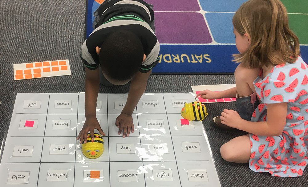 Two students work with Bee-Bots on a floor mat