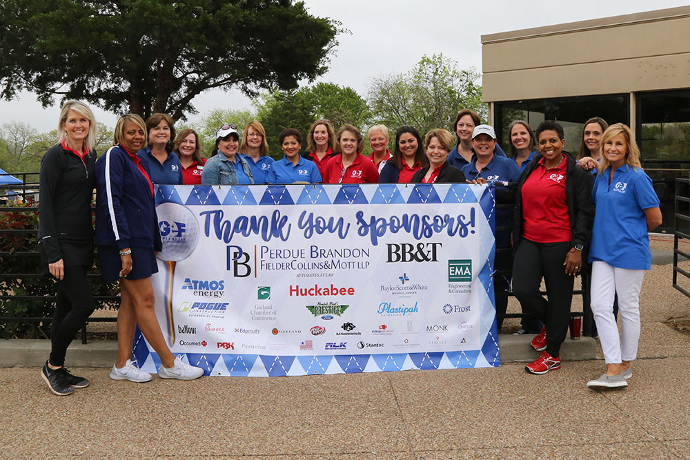 Volunteers and district staff pose with sponsor banner.