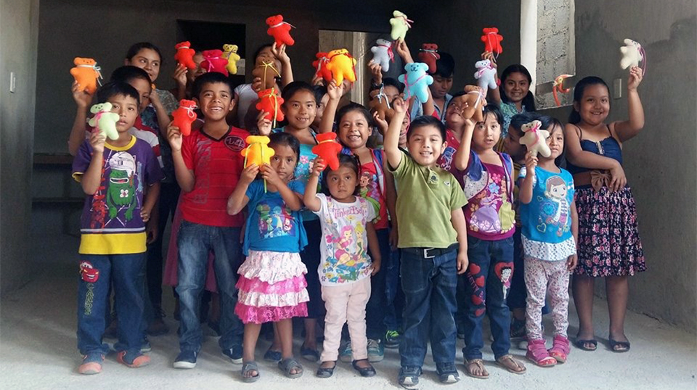"Children from Mexico show off their creations from the ""Sew Much Love"" club."