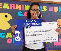 Grant recipient, Tameko Brigham, holds up her GEF check.